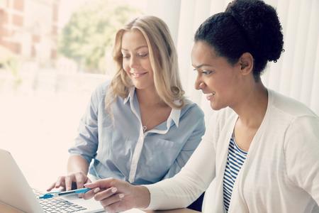 dos personas platicando: Dos mujeres que trabajan juntos en la oficina