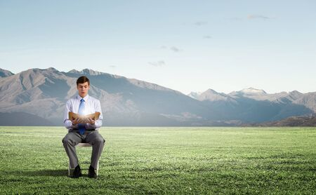 solver: Businessman sitting in chair and reading book Stock Photo