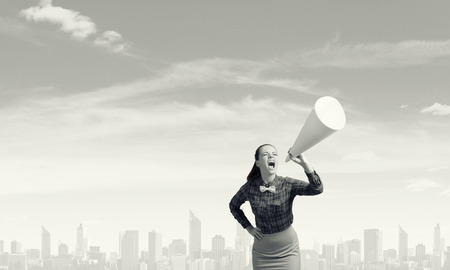 speaking trumpet: Young pretty woman screaming in paper trumpet Stock Photo