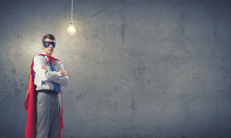 powerful creativity: Young confident super guy in mask and cape Stock Photo