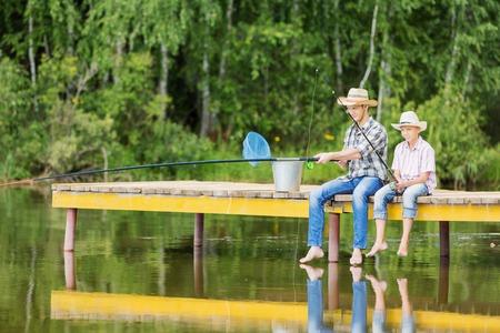 pescando: Padre e hijo sentado en el puente y la pesca Foto de archivo