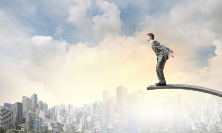businessman jumping: Young businessman jumping from springboard in to deep Stock Photo