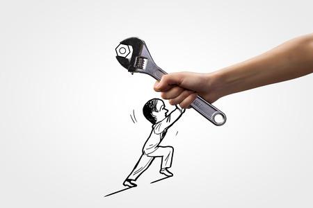ingeniero caricatura: La mano del hombre y la caricatura de hombre tratando de mover la llave