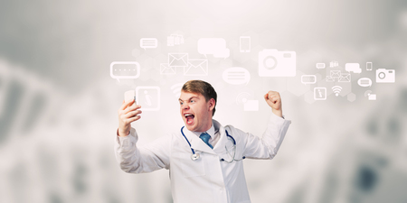 emotionally: Young male doctor screaming in mobile phone emotionally Stock Photo
