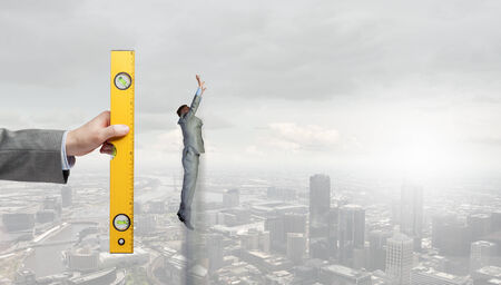 businessman jumping: Hand measuring businessman jumping high in sky Stock Photo