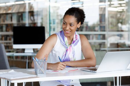succesful: Portrait of a young business woman working on a laptop in a office Stock Photo