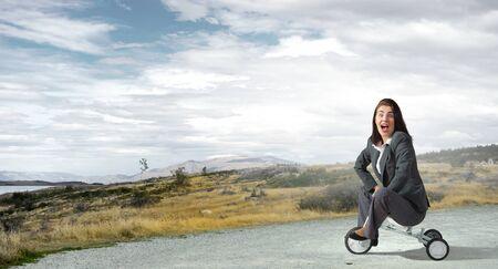 wheeled: Young pretty businesswoman riding three wheeled bike