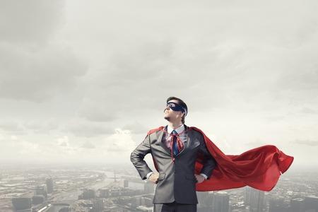 confianza: Joven súper empresario confía en máscara y la capa