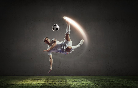Football player in high jump taking ball Stock Photo