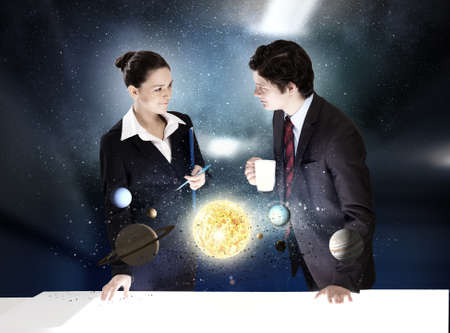 Young businesswoman and businessman and planets of space spinning around photo