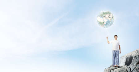 Young handsome smiling guy with balloon in hand against sky background.  photo