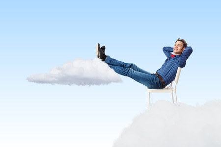 office break: Young man sitting in chair with legs up and relaxing