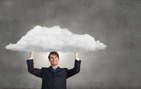 above head: Young businessman holding media cloud above head