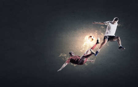 Two football players in jump fighting for ball photo