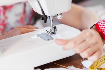 Close up of woman dressmaker hands working with sewing machine