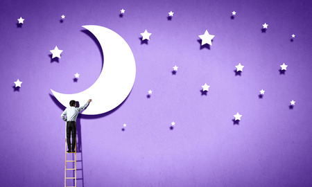 man in the moon: Rear view of man standing on ladder and reaching moon