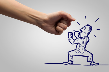 fight: Close up of human fist fighting with businessman caricature