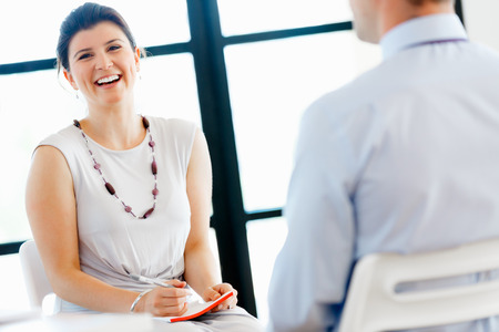 women talking: Business woman talking to her collegues in office Stock Photo