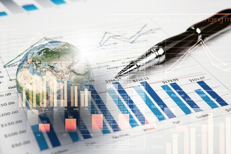 Background image with financial charts and graphs on the table.