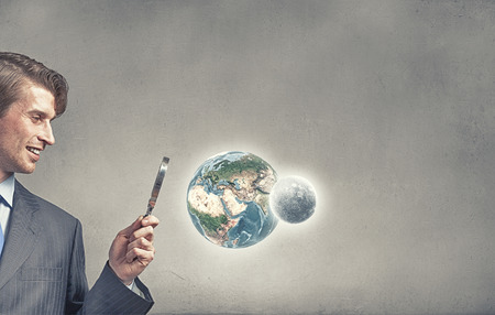 optical people person planet: Businessman exploring Earth planet with magnifier.  Stock Photo