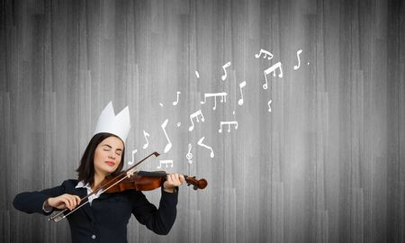 virtuoso: Young pretty businesswoman in paper crown playing violin
