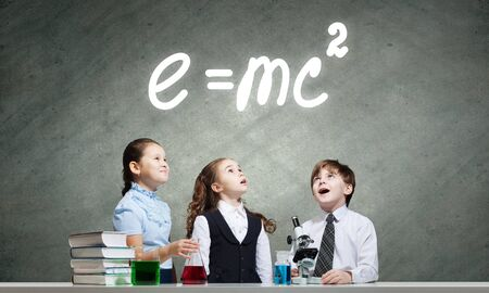 chemistry lesson: Three cute children at chemistry lesson making experiments Stock Photo