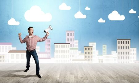 man screaming: Young funny man screaming emotionally in megaphone Stock Photo