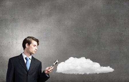 examining: Smiling businessman examining cloud with magnifying glass