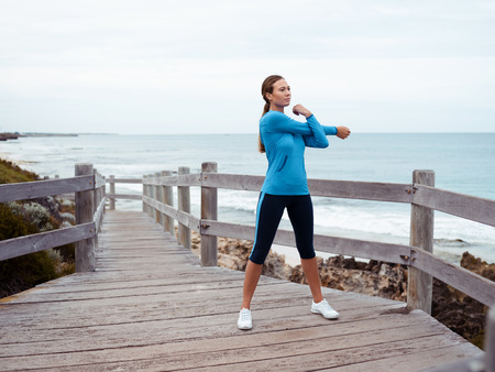 activewear: Sporty young woman on the sea coast