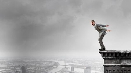 businessman jumping: Determined businessman jumping in deep from edge of building