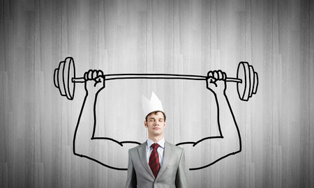 above head: Young businessman in paper crown lifting barbell above head Stock Photo