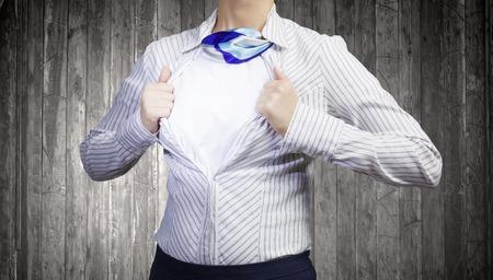 Unrecognizable businesswoman opening her shirt like superhero Foto de archivo