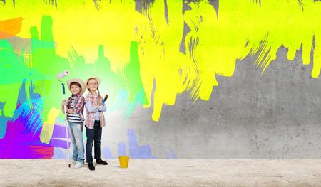 Dwoje dzieci w wieku szkolnym, malowanie ściany w kolorze