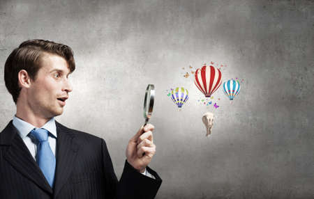 optical people person planet: Businessman with magnifying glass amused with discovery Stock Photo