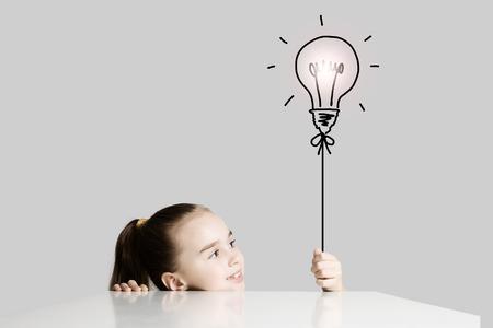 imaginacion: Ni�a linda de la escuela y la bombilla el�ctrica Foto de archivo