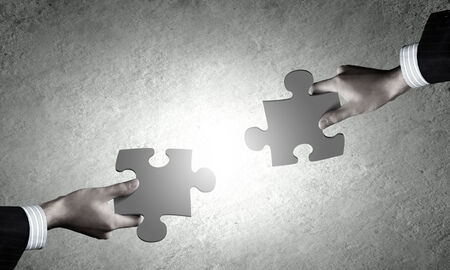 connective: Close up of human hands connecting puzzle elements