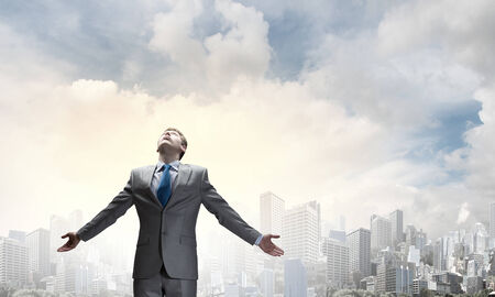 Joyful businessman with outstretched arms celebrating success Stock Photo