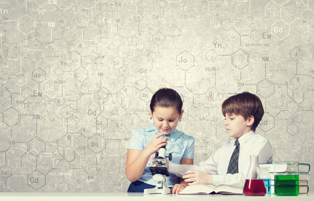 chemistry lesson: Cute girl and boy at chemistry lesson making tests Stock Photo
