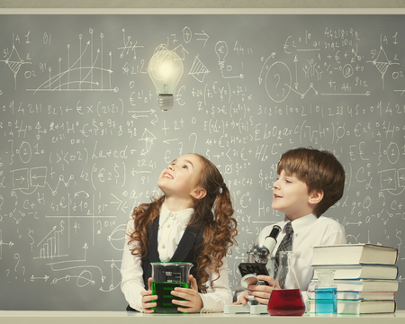 Cute girl and boy at chemistry lesson making tests photo
