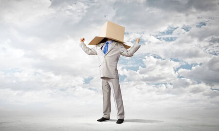 hidden success: Businessman wearing carton box with drawn emotions on head Stock Photo