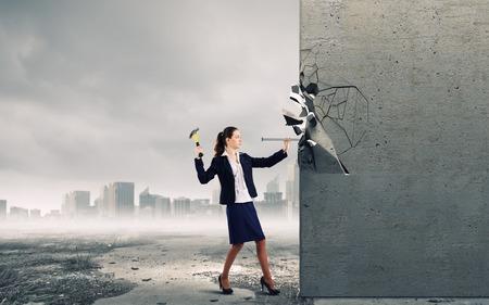 ハンマーで壁に釘を打つ若い実業家