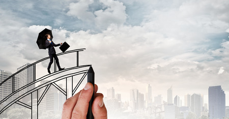 Confident businessman walking on drawn bridge over gap
