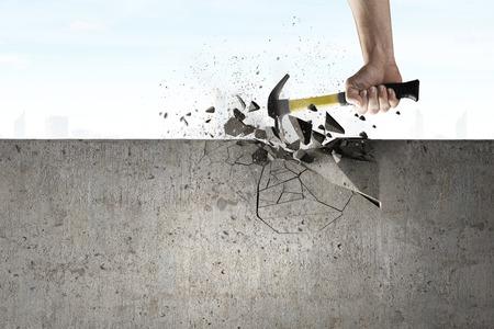 martillo: Cierre de martillo en mano rompiendo la pared de cemento