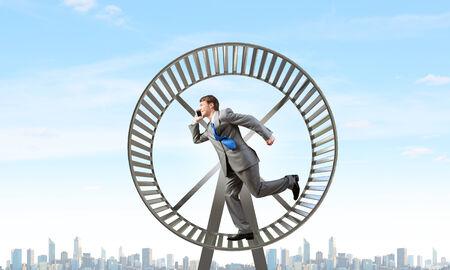 businessman running: Young businessman running in huge hamster wheel Stock Photo