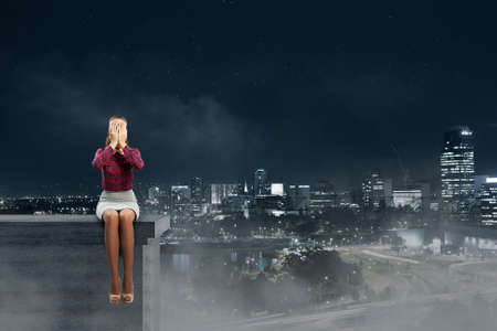 fear of failure: Young woman sitting on building top and covering face with palms