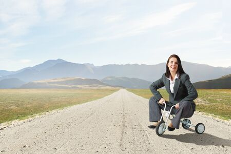 Young pretty businesswoman riding three wheeled bike photo