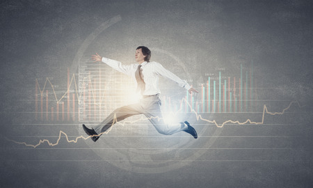 Businessman with briefcase jumping against digital background photo