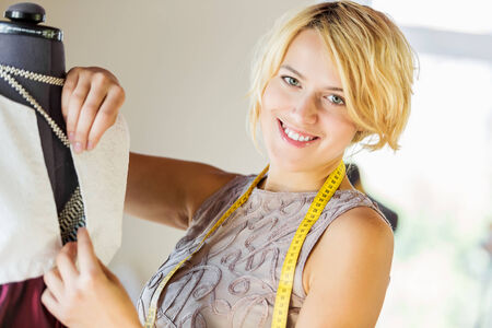 pinning: Pretty dressmaker at work pinning dress on dummy