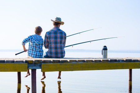 boy and his father fishing together from a pier 스톡 콘텐츠