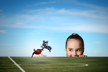 Little girl looking at two football players photo